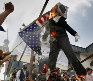 Muslims burn an effigy of Pastor Terry Jones who may burn a copy of the Koran